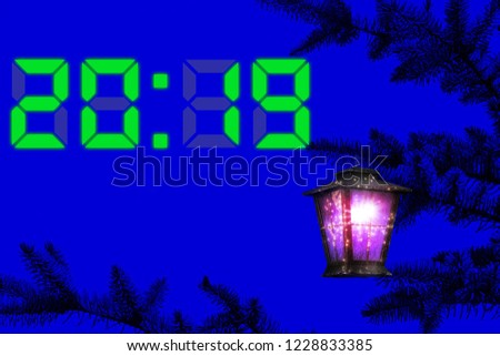 2019 New Year and time. Vintage colorful lantern hangs on a Christmas tree against the dark blue night sky. Magical lighting with sparkles #1228833385