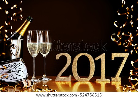 2017 New Year celebration with a bottle and flutes of chilled champagne, golden party streamers and a modern clock counting down to midnight, copy space for your greeting #524756515