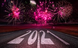 2021 New Year celebration with fireworks on horizon and text number on the road asphalt. New Year arrival concept
