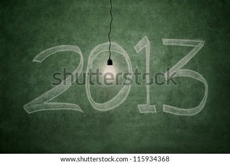 2013 new year concept: an electric light bulb glowing bright in front of blackboard symbolizing good year