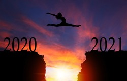 2021 New Year concept with silhouette of courageous girl leaping over cliff with dramatic sunset or sunrise background and copy space. Concept of going from Year 2020 to 2021.