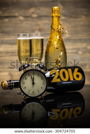 2016 New Year concept with the date in numbers, clock and bottle of champagne