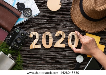 2020 new year eve trip.top view hand putting happy new year number on wood table with adventure accessory item,holiday vacation resolutions planning