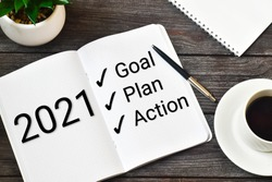 2021 New Year. Goal,plan, action text on notepad with office accessories on a wooden background. Business motivation, inspection concepts ideas.