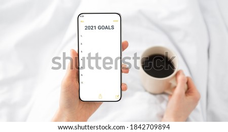 2021 New Year Goals Checklist. Hands Holding Smartphone With Future Goal And Plans List For Upcoming New Year Making Yearly Planning For 2021 Lying In Bed Indoor. Panorama, Selective Focus, Cropped