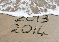 New Year 2014 is coming concept - inscription 2013 and 2014 on a beach sand, the wave is starting to cover the digits 2013