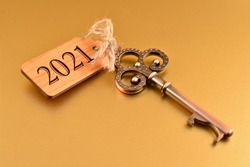 2021 New Year Key stock images. Old decorativekey with wooden tag 2021 isolated on a golden background. Golden New Year 2021. Key with number 2021 stock images