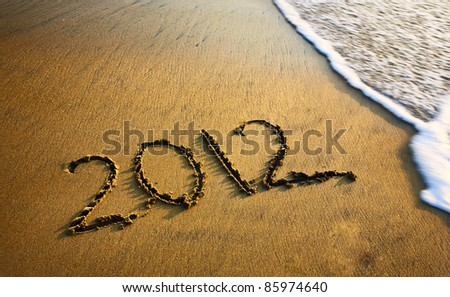 2012 new year message on the sand beach near the ocean. Free space for text