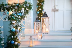 New Year's decor in a blue veranda with a garland of blue, blue and gold balls. Great gifts, mailbox and Christmas tree. Decorative lanterns with candles