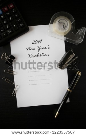 2019 New Year's Resolution on black table with stationery. New Year's Resolution flatlay on a paper with pen, stapler, clips.