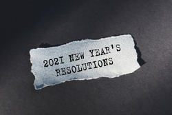 2021 New Year's Resolutions - text on torn paper on dark desk in sunlight