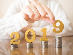 2019 New year saving money and financial planning concept. Female hands putting gold wooden number 2019 on stack of coins. Creative idea for business growth, tax payment, investment and banking.