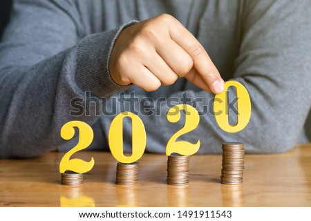 2020 New year saving money and financial planning concept. Female hands putting gold wooden number 2020 on stack of coins. tax payment, investment and banking.