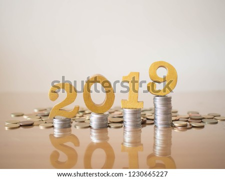 2019 New year saving money and financial planning concept. Stack of coins w/ gold number 2019 on wood table. Creative idea for business growth, tax payment, investment and banking.