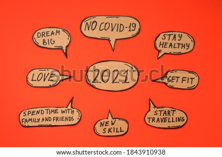 Photo of  2021 new year wishes written on cartoon bubbles on red background. Resolutions are: no covid-19, stay healthy, get fit, start traveling, new skill, spend time with family and friends, love, dream big