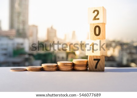 2017 NEW YEAR with stacked coins on wooden block. Business and Financial concept. #546077689