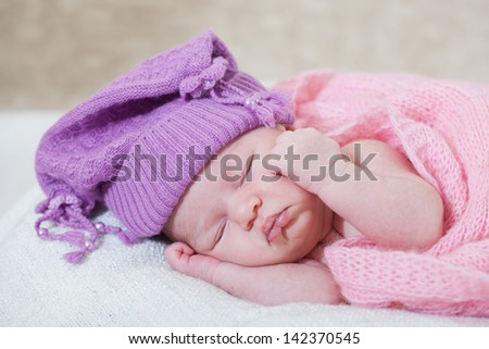newborn girl in a violet hat sleeps under a pink cape