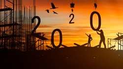 2020 newyear silhouette The man is standing, commanding the crane to bring the two to the ground,2020 concept happy new year.