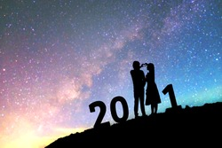 2021 Newyear Silhouette young couple Happy for romantic background on the Milky Way galaxy pointing on a bright star.