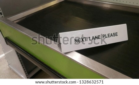 'Next Lane Please' holder is put on convenient store's cashier counter, informing customers to use service at other counters