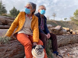 Nice adult couple outdoors in winter clothes and with mask walking in the woods with their pug dog