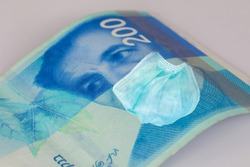 200 NIS money bill with face mask. COVID-19 affects in ISRAEL. Coronavirus  Crisis and finance concept.