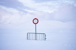 no entry or transit, on a snow-covered road, over one meter of snow. desolation and silence in an abandoned landscape.