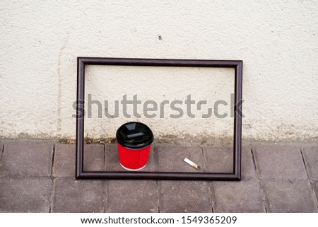 no healthy habits concept. Red cup of coffee and a cigarette butt in a frame