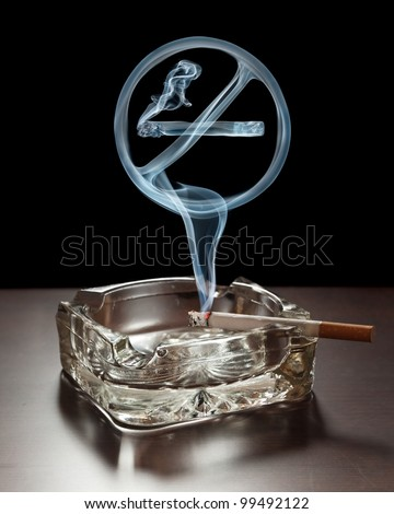 """No smoking"" smoke sign rising from a cigarette in an ashtray."