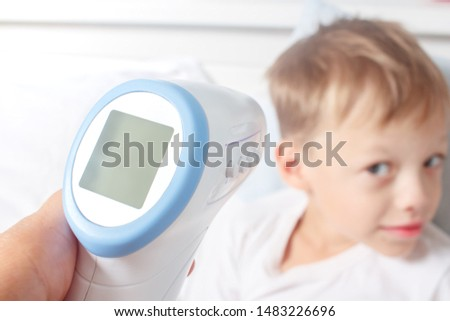 Non-contact digital infrared thermometer in the hands of the mother of a sick boy. Monitoring and measuring the temperature of colds and flu.  Cold season concept. #1483226696