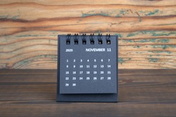 2020 NOVEMBER. Black paper calendar on a wooden table. Time planning, day counting and holidays