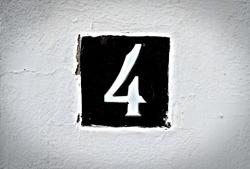 4, number 4, black tile on a white background, vignetted.
