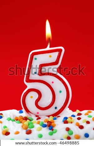 Number five birthday candle on red background