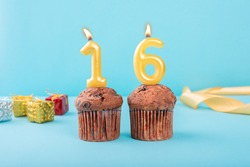 16 Number gold candle on a cupcake against a pastel blue background sixteen year celebration