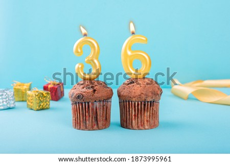 36 Number gold candle on a cupcake against a pastel blue background thirty sixth year celebration Foto stock ©