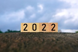 2022 number on wooden block on top of big stone - 2022 new year concept
