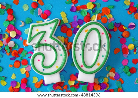 Number thirty birthday candle on blue background
