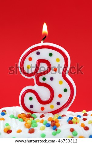 Number three birthday candle on red background