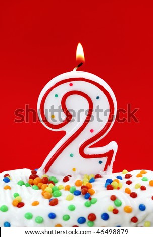 Number two birthday candle on red background