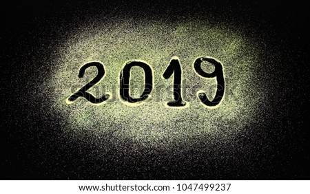 2019 numbers written with finger in gold dust glitter isolated on black background. Gold Happy new year 2019 invitation banner or wallpaper. #1047499237