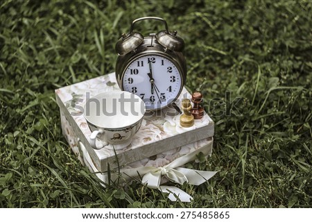 6 o\'clock - tea time. An alarm clock, a tea cup and two pawns on a present box.