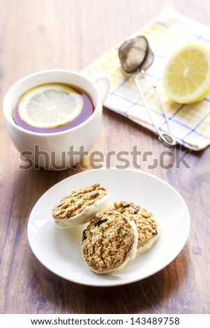 3 oatmeal raisin cookies on white plate and cup of tea with lemon slice in it