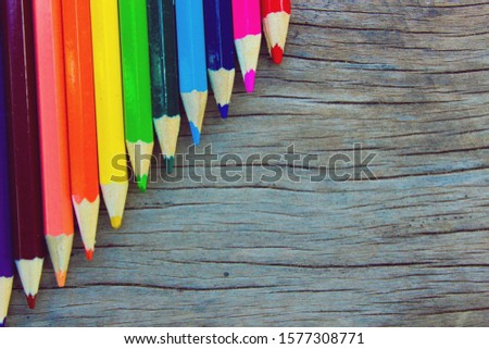 [object Object]Bright colored pencils used to paint the image. There are green, yellow, red, blue, purple, black, blue, brown on the old wooden floor.