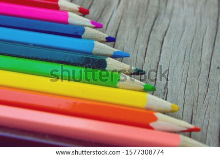 [object Object]Bright colored pencils used to paint the image. There are green, yellow, red, blue, purple, black, blue, brown on the old wooden floor. #1577308774