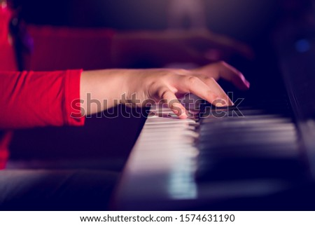 [object Object]Closeup kid's hand playing piano on stage with lighting. Favorite classical music. There are musical instrument for concert or learning music. The concept of musical instrument.