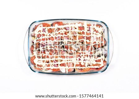 [object Object]In a glass pan stacked pieces of fish doused with mayonnaise under it potatoes with onions and spices top view