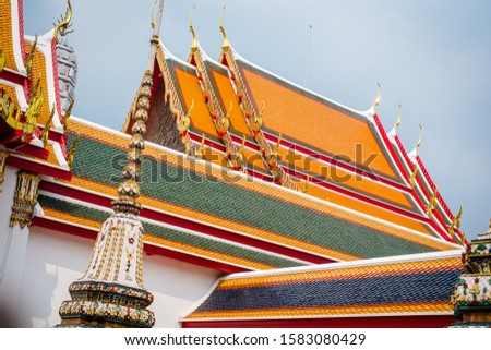 [object Object]Young buddhist monks walking up the stairs to Thai temple in Bangkok, Thailand.