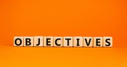 'Objectives' written on wooden blocks. Business concept. Copy space. Beautiful orange background.