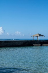 Ocean Pier With Sunlight and Blue Skies.  Profile view of an empty pier and beach during the corona virus pandemic.