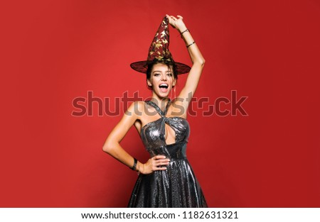 31 october - celebration party. Surprised woman in witches hat and short dress. Glamour Fashion Sexy Vampire Lady with witch costume #1182631321